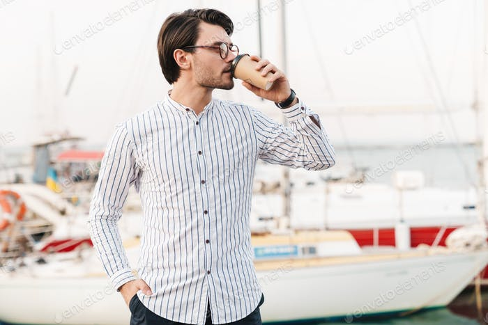 Photo of successful masculine man standing and drinking coffee from paper cup while walking on pier