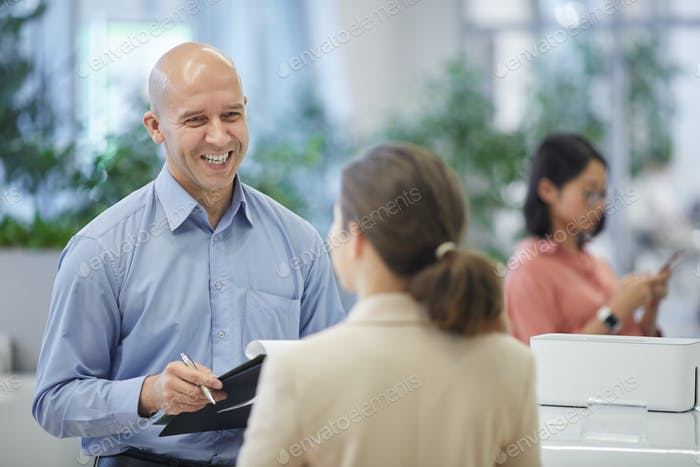 Smiling Bald Businessman Talking to Female Client