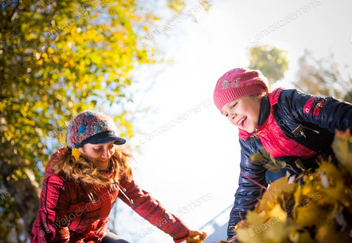 Charming mom and cheerful daughter in the park