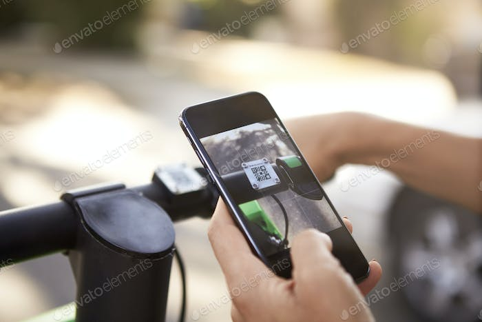 Close up of woman's hands using smartphone while riding on an electric scooter,detail