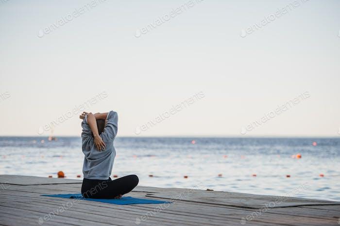 Pretty woman practicing yoga at a lake