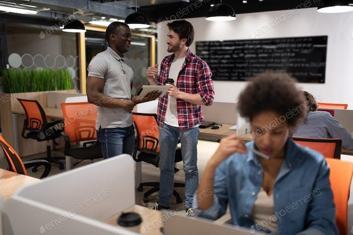 Diverse Männer mit Tablet sprechen im Büro