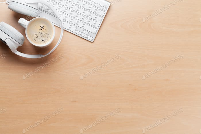 Headphones over keyboard and coffee cup