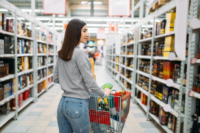 Woman with cart in alcohol drinks department