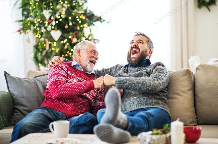 A senior father and adult son sitting on a sofa at home at Christmas time, laughing.