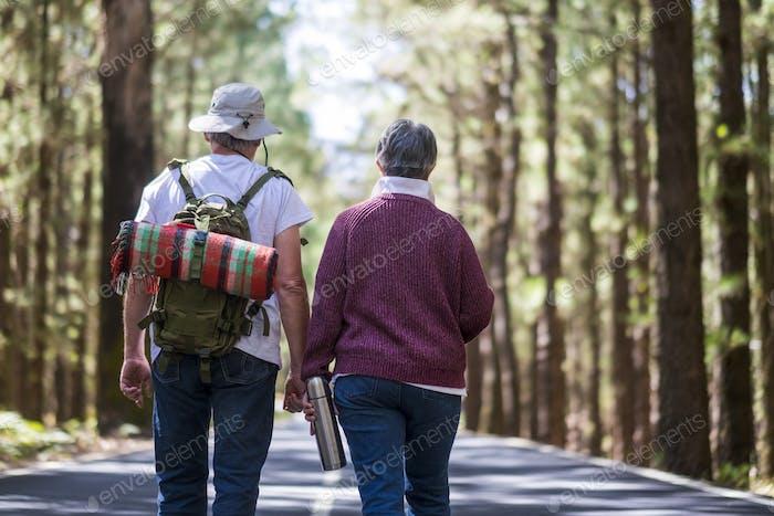 Ein paar ältere Senioren spazieren mitten auf einer Straße mit Wald