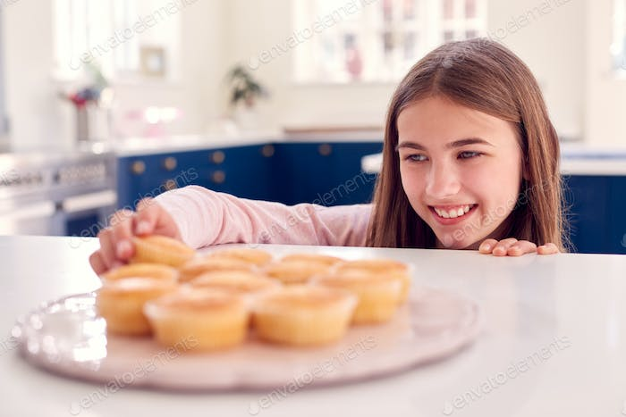 Teenage Girl Taking Freshly Baked Homemade Cupcake From Plate In Kitchen At Home