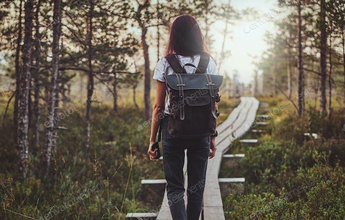 Skinny Frau wandert durch den Holzweg in der Mitte des üppigen Pinienwaldes.