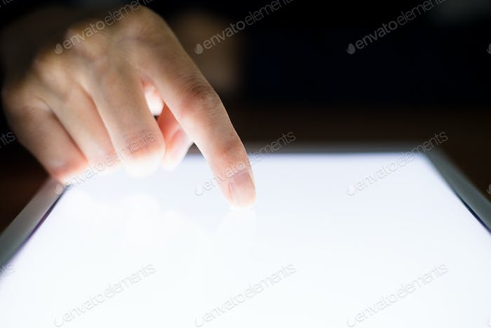 Woman with finger touch on digital tablet at night