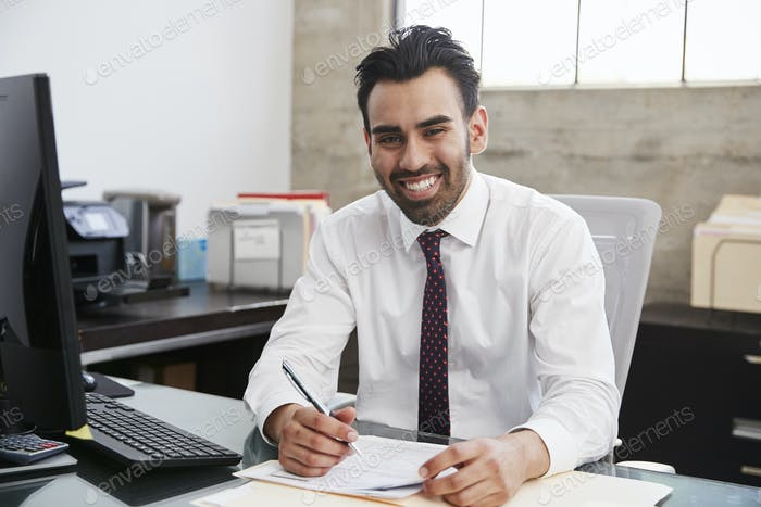 Young Hispanic male professional at desk smiling to camera