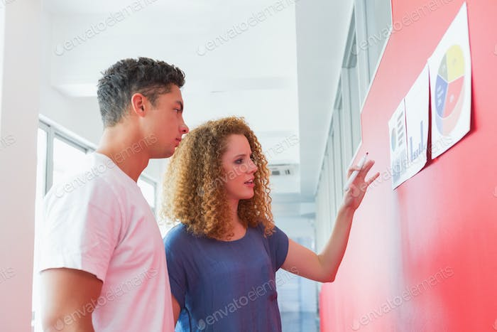 Students studying together with graphics on the wall at the college