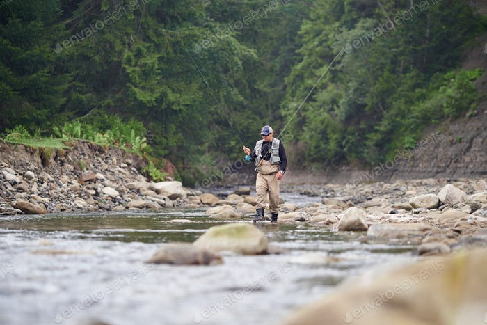 Fisherman walking in river with two professional rods