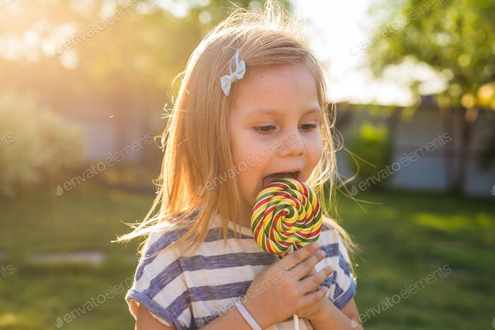 cute cauasian baby girl and big lollipop