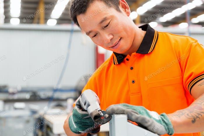 Trabajador asiático en planta de producción en el piso de la fábrica