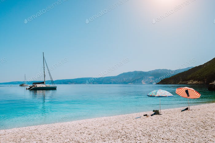 Idyllic white beach with umbrellas on lazy summer day. Sailing boat on calm crystal clear water