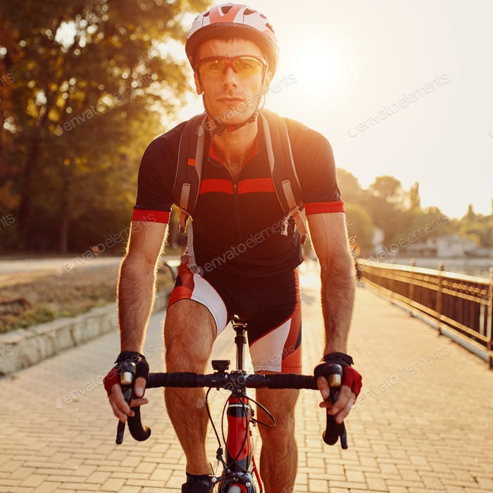 Young man are cycling road bike in the evening