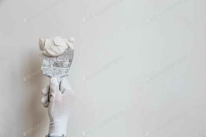 Arbeiter in weißen Handschuhen führt Verputzen der Wände des Raumes durch
