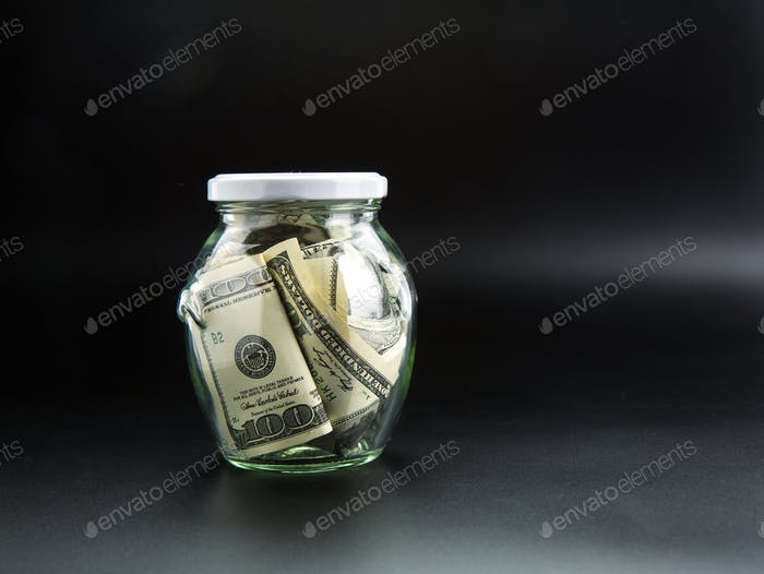 Money saving concept, glass jar full of dollars