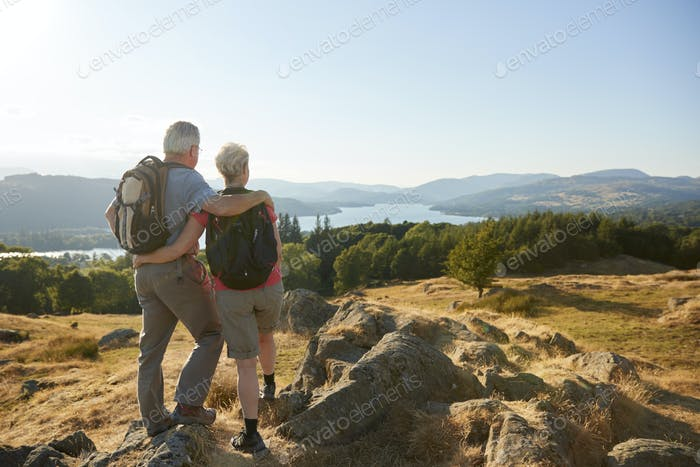 Rear View Of Senior Couple Standing At Top Of Hill On Hike Through Countryside In Lake District UK