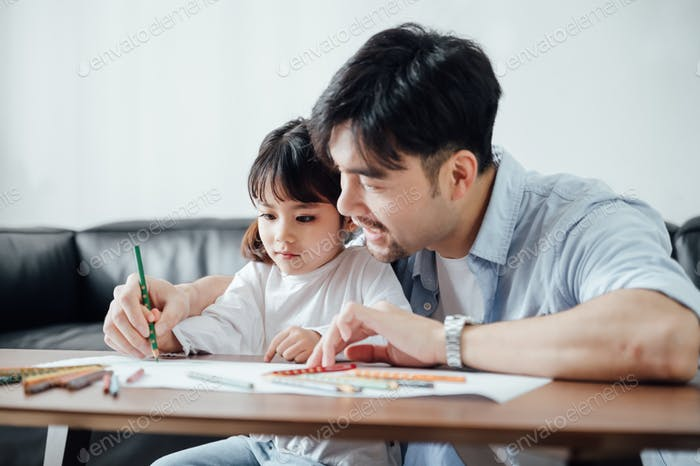 Father and daughter drawing together at home