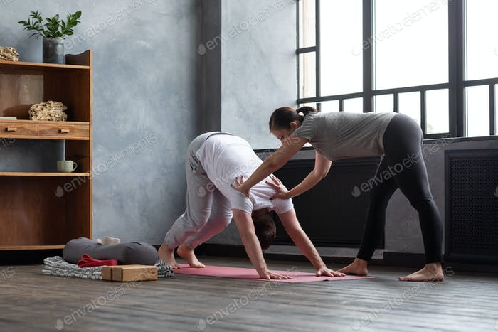 Yoga teacher or pilates instructor helping young man to stretch muscles