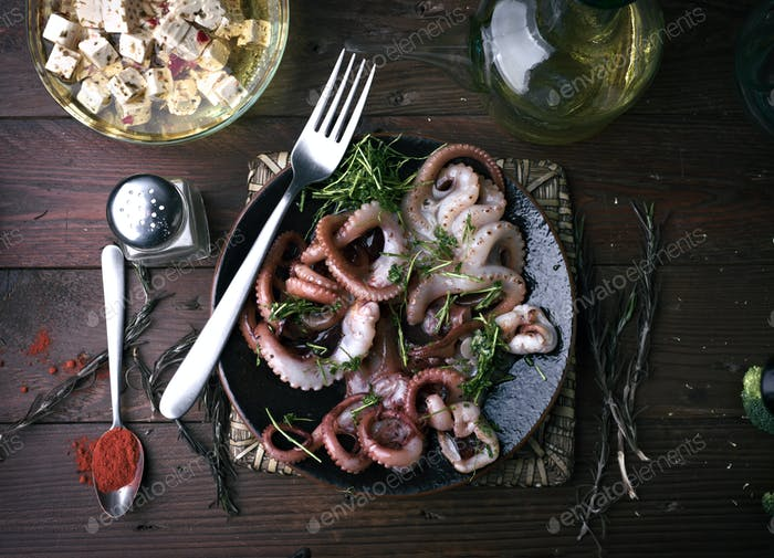 Octopus cooked with parsley and oil in a porcelain dish on rustic wood