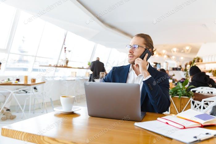 Konzentrierter junger Geschäftsmann im Gespräch per Handy.
