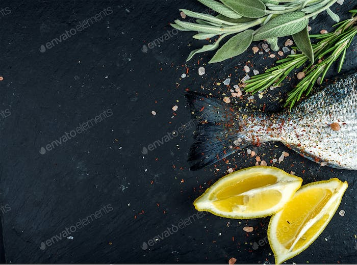 Tail of fresh raw Dorado or sea bream fish on black slate stone board with spices