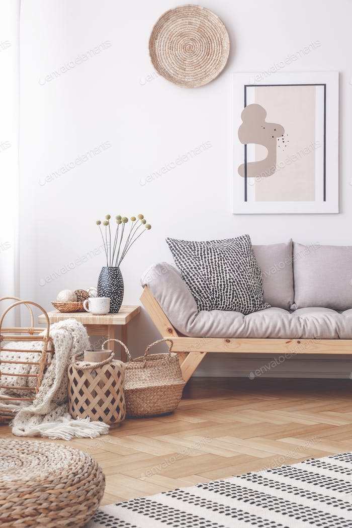 Baskets and pouf on wooden floor in living room interior with po