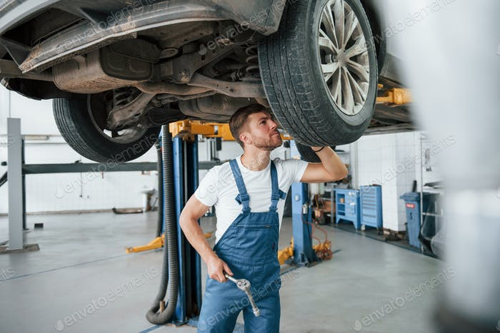 Take closer look. Employee in the blue colored uniform works in the automobile salon