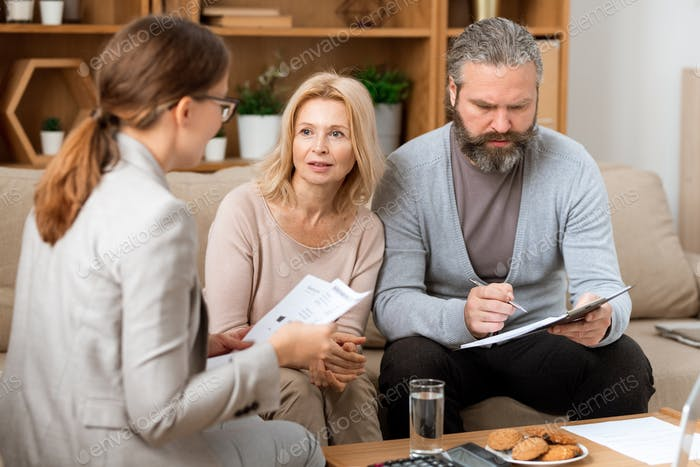 Mature woman consulting with real estate agent while her husband reading paper