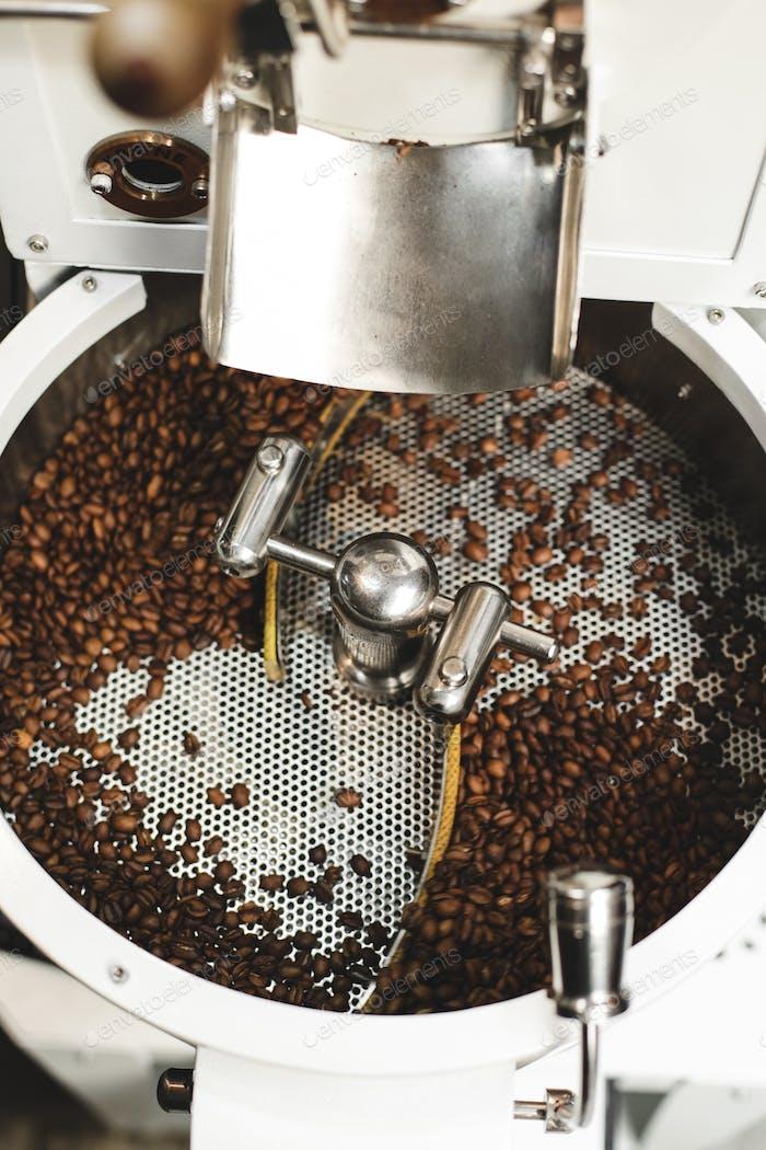 Frisch geröstete Kaffeebohnen in einer modernen Kaffeeröstermaschine