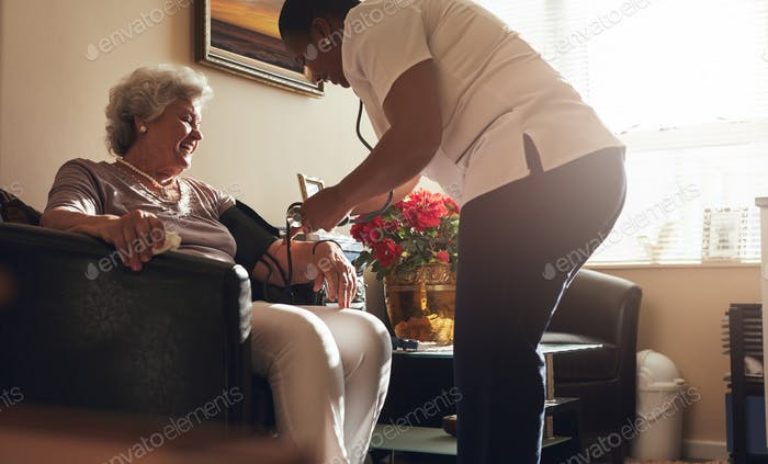 Female healthcare worker taking blood pressure of senior patient