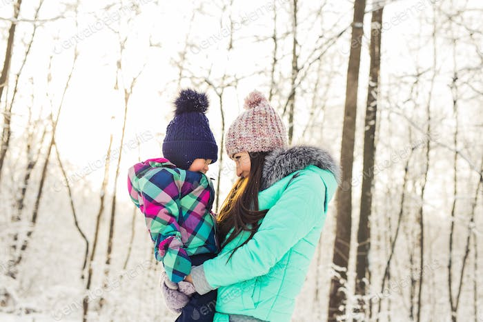 Mother and daughter having fun in the winter park
