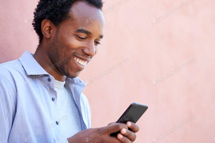 Outdoor-Porträt des Menschen mit Handy In Der Straße An die Wand gelehnt