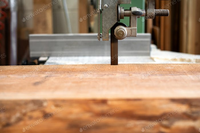 Sawing wood using a band saw in a workshop