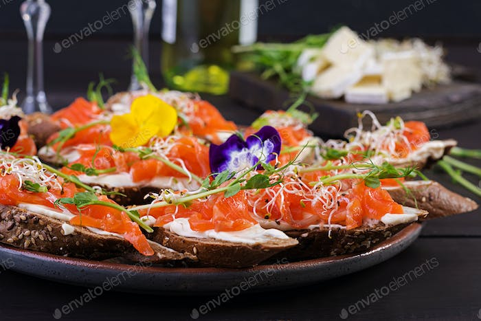 Salmon sandwiches with cream cheese and microgreen on wooden table. Canape with salmon.
