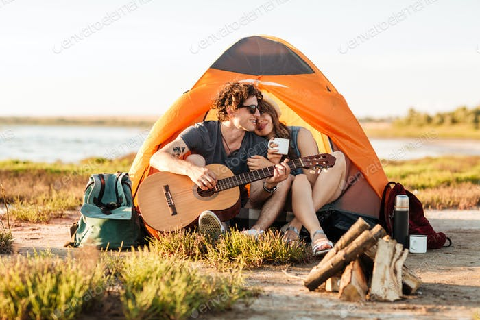 Portrait of a man playing guitar for his girlfriend camping