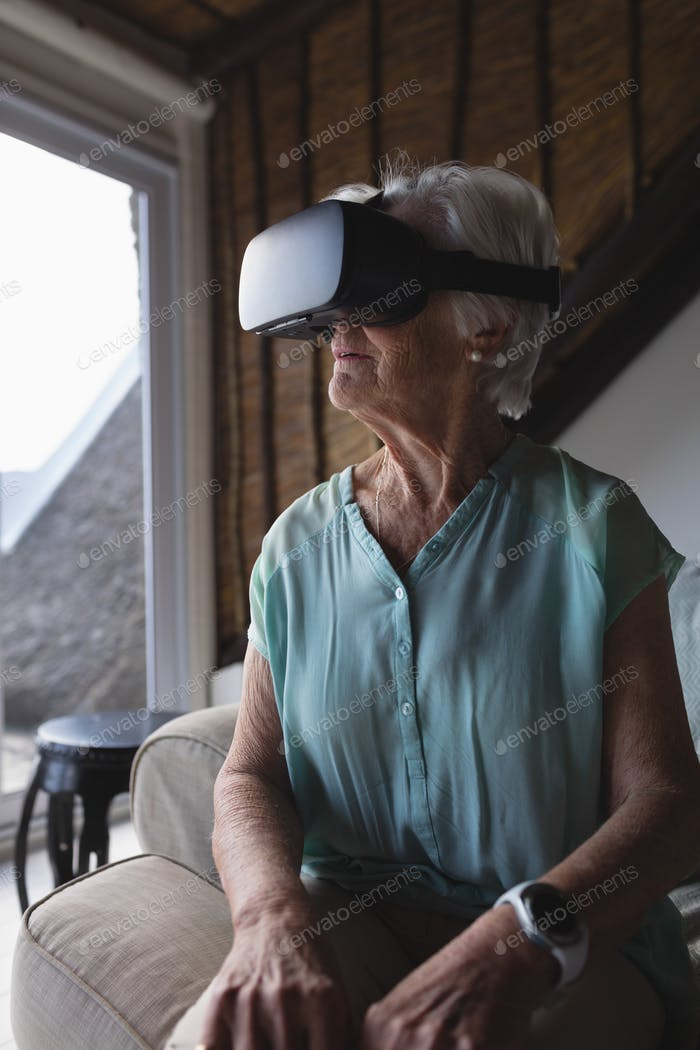 Front view of a senior woman using virtual reality headset in living room at home
