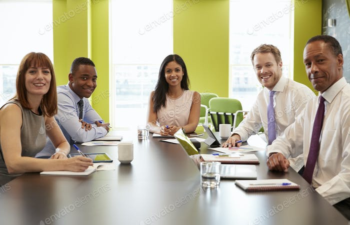 Business colleagues at an informal meeting look to camera