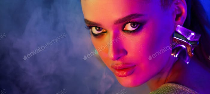 Sexy girl posing in neon light and smoke