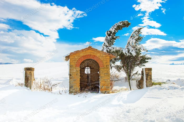 Tuscany, chapel and trees covered by snow in winter. Italy