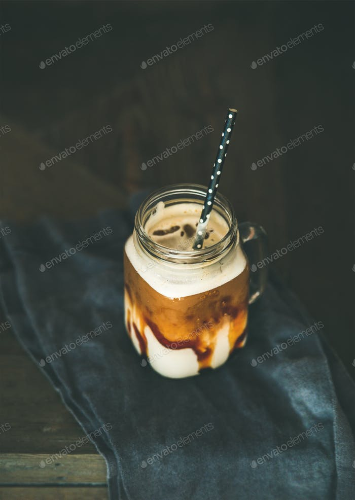 Iced caramel macciato coffee with milk in jar with straw