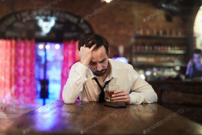 Depressed Man Drinking in Bar