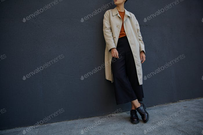 Cropped photo of young hipster woman dressed in black culottes, foxy sweater and beige trench