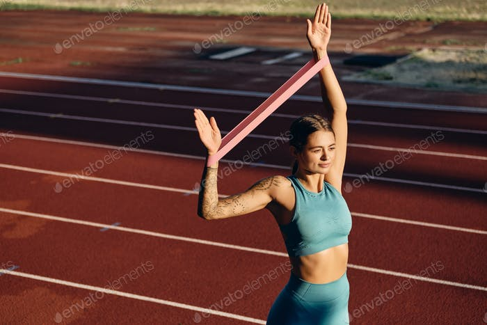 Athlete girl in sportswear stretching hands with rubber band during workout on city stadium