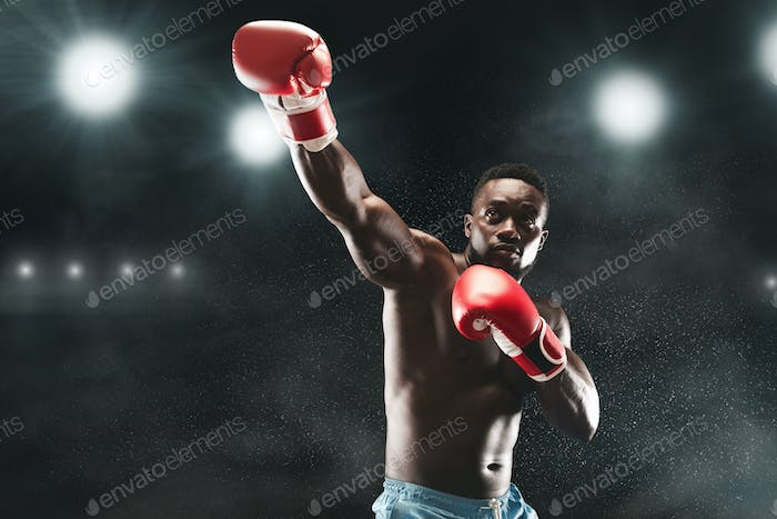 Picture of professional black mma boxer fighting on stadium arena