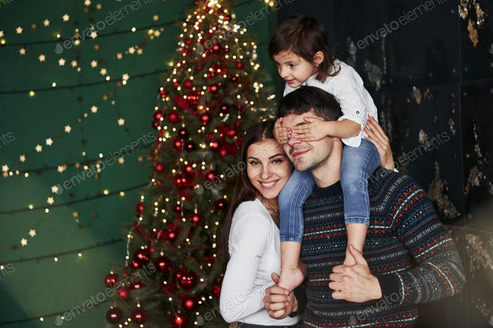 Girl sits on the father's shoulders and covering his eyes. Decorated Christmas at background