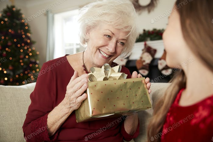 Excited Grandmother Receiving Christmas Gift From Granddaughter At Home