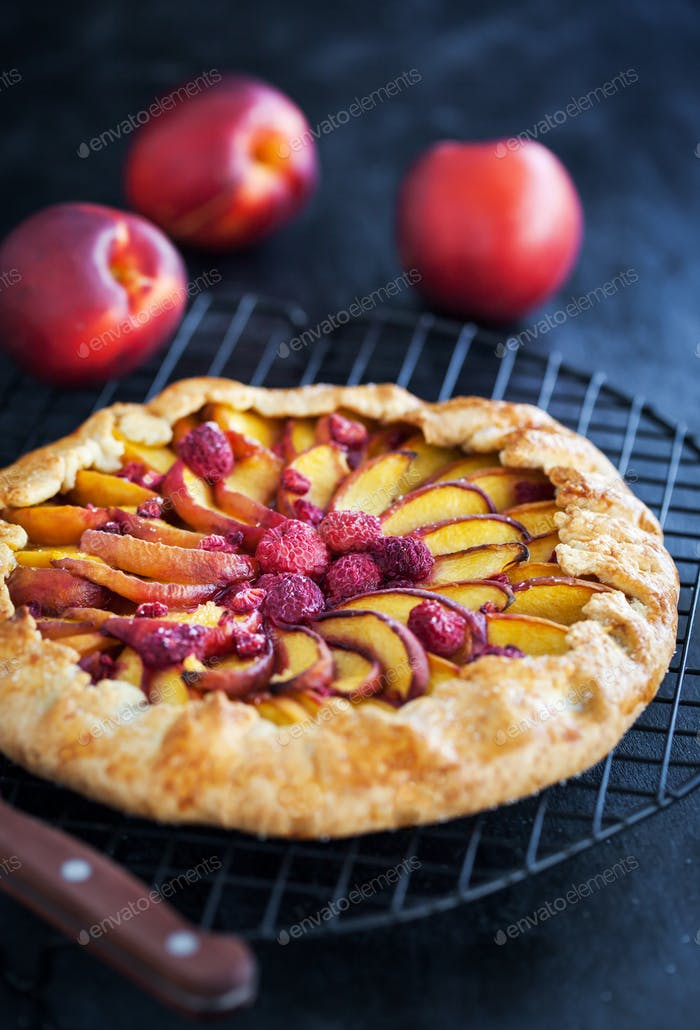 Galette with peach and raspberry on dark